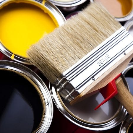 A large paint brush laying on top of open paint cans