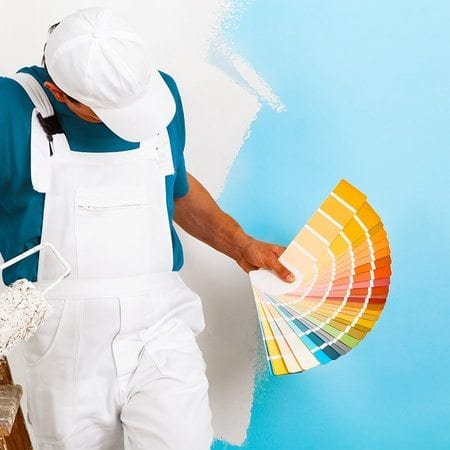 An industrial painter in white overalls holds a rainbow of color samplers in front of a freshly painted white and blue wall